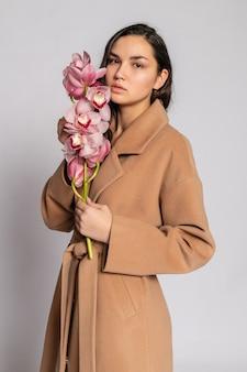회색 배경에 스튜디오에서 포즈를 취하는 갈색 재킷에 매혹적인 금발 여자. 파스텔 캐주얼 봄 옷을 입은 우아한 모델의 패션 초상화. 건강한 피부와 가지 난초를 가진 아름다운 소녀