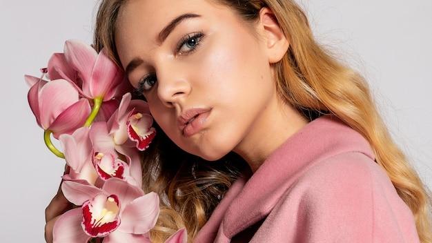 회색 배경에 스튜디오에서 포즈를 취하는 분홍색 재킷을 입은 매혹적인 금발 여성. 파스텔 캐주얼 봄 복장에 우아한 모델입니다. 건강한 피부와 난초를 가진 아름다운 소녀. 16:9 파노라마 형식.