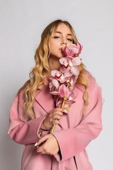 회색 배경에 스튜디오에서 포즈를 취하는 분홍색 재킷을 입은 매혹적인 금발 여성. 파스텔 캐주얼 봄 옷을 입은 우아한 모델의 패션 초상화. 건강한 피부와 가지 난초를 가진 아름다운 소녀