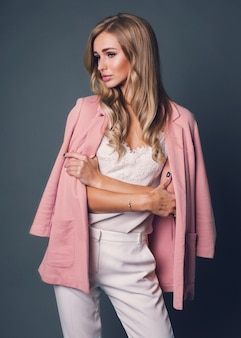 Seductive blonde woman in pink jacket posing