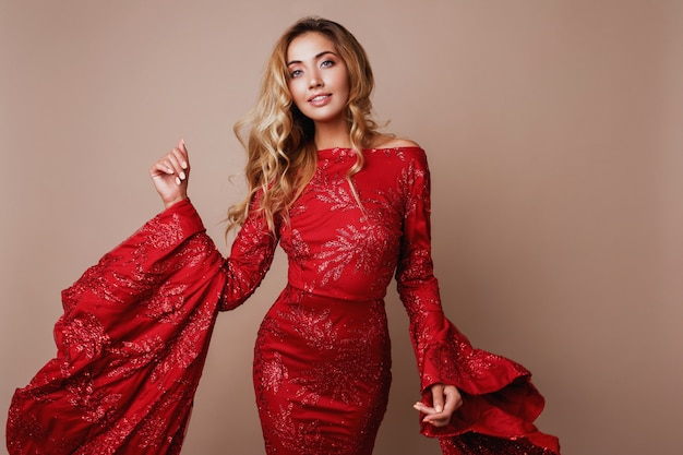 Seductive blonde woman posing in luxury red dress with wide sleeves. fashionable look. blond wavy hairs.