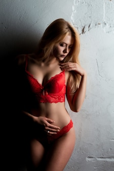 Seductive blonde woman with long hair in red lace lingerie posing in the dark room