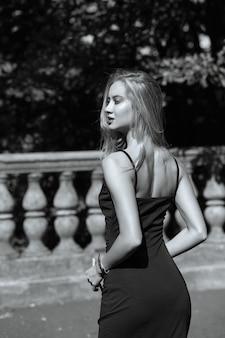 手すり子の近くでポーズをとって、ドレスを着て長い髪の魅惑的なブロンドの女性。モノクロ調色