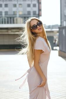 일몰에 거리를 걷고 있는 분홍색 드레스를 입고 긴 머리를 가진 매혹적인 금발의 여자