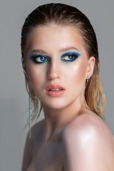 Соблазнительная блондинка с мокрыми волосами и темно-синим макияжем с дымчатыми глазами
