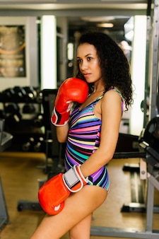 Seductive boxer model wearing big gloves and posing in fitness gym