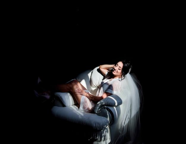 Соблазнительная невеста в белом халате сидит на мягком стуле в темной комнате