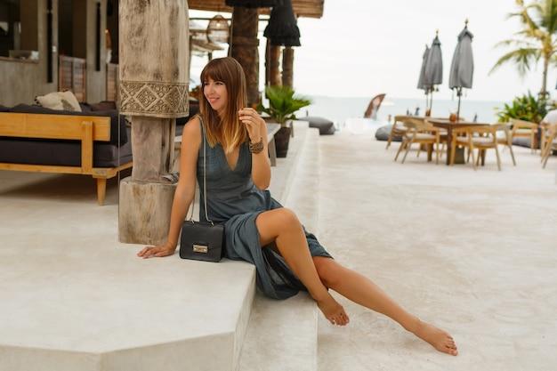 아시아 스타일의 세련된 해변 레스토랑에서 포즈 섹시 드레스에 매혹적인 갈색 머리 여성.
