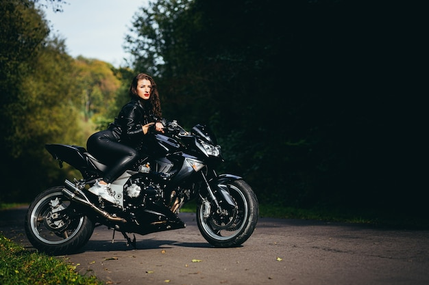Seductive brunette girl with long hair in a black leather jacket sits near a modern motorcycle on a background of nature. closeup portrait of a sexy woman near an expensive black bike.