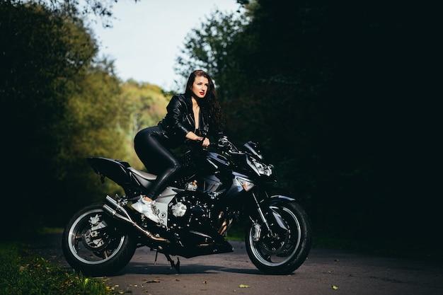 Соблазнительная брюнетка с длинными волосами в черной кожаной куртке сидит возле современного мотоцикла на фоне природы. крупным планом портрет сексуальная женщина возле дорогого черного велосипеда.