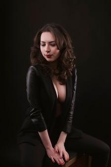 スタジオで革のジャケットの魅惑的なブルネットの女性