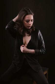 暗闇の中でポーズをとる魅惑的なブルネットの女性