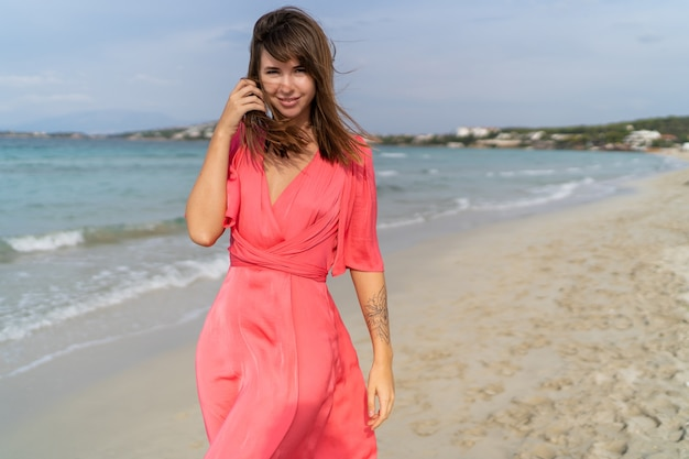 Seductive brunette woman  with tatoo on hand in pink dress posing on the beach.