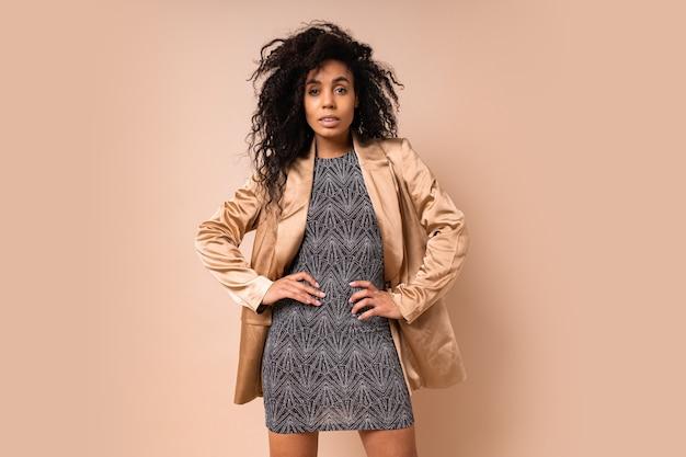 Donna elegante seducente con pelle scura e incredibili capelli ricci in vestito splendente da festa e giacca di raso in posa.
