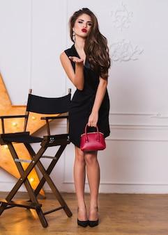 Donna alla moda seducente in vestito nero elegante e gioielli in posa incredibile. manda un bacio ai camer