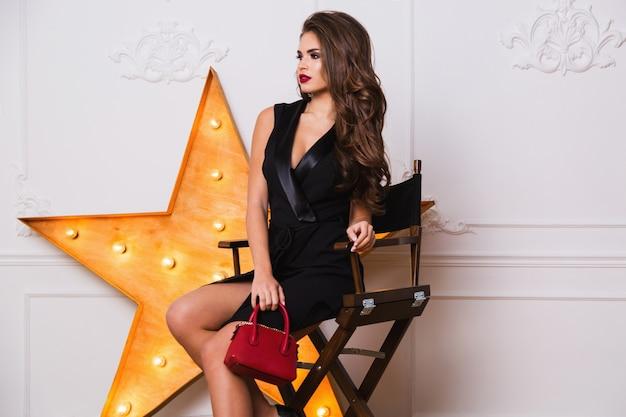 Соблазнительная модная женщина в элегантном черном платье и удивительных украшениях сидит на стуле