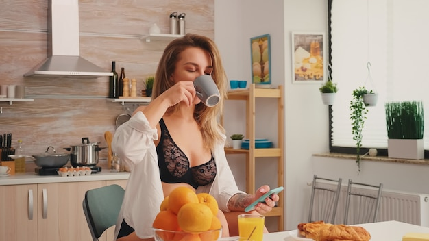 Seductive housewife with tattoos using smartphone wearing temping underwear drinking coffee in the morning. attractive blonde lady in lingerie holding a cup of tea during breakfast enjoying the time.