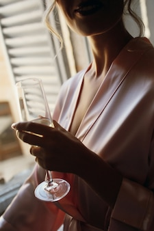 Seductive lady in pink silk robe holds champagne flute