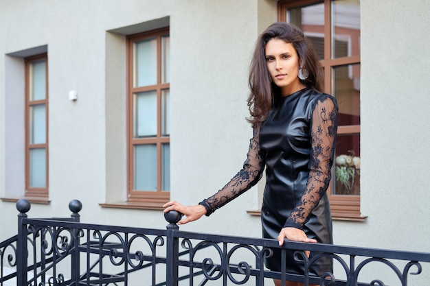 Seductive lady in short leather dress descending the stairs