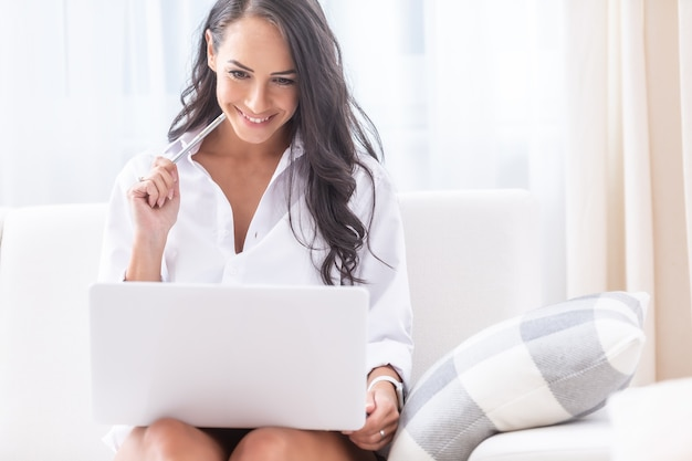 Seductive looking young female holding a pen in hand close to her face sitting dressed only in her white shirt in her bright living room, looking into a notebook on her knees.