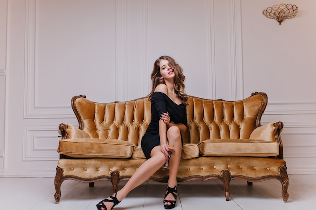 Seductive, mysterious european female aristocrat with long curls, red lipstick and in elegant black dress posing on royal sofa in bright room
