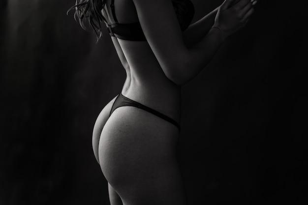 검은색 비키니를 입은 검은 머리 여자의 매혹적인 포즈