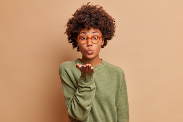 Seductive pretty girl with afro hair sends mwah at front makes air kiss gesture flirts with you keeps lips folded expresses admiration looks tenderly dressed casually poses indoor