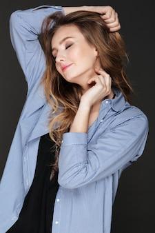 Giovane donna rilassata seducente nella condizione e nella posa della camicia a strisce
