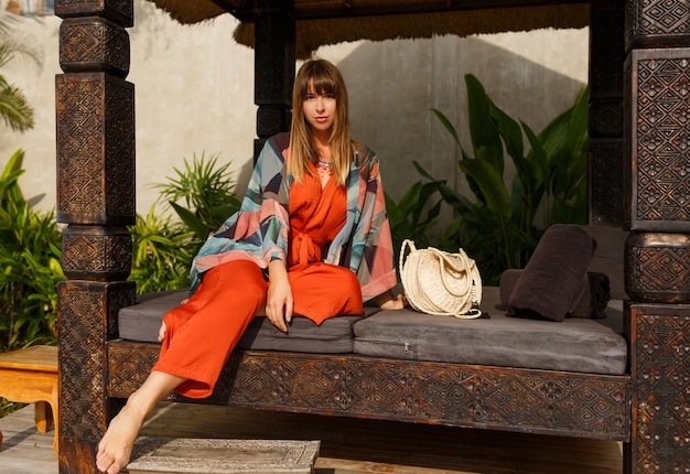 Seductive stylish woman in bohemian summer clothes  posing in tropical luxury resort. vacation  concept.