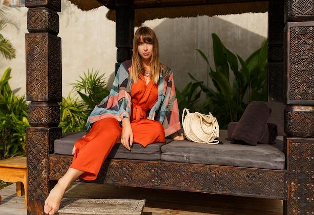 トロピカルラグジュアリーリゾートでポーズをとる自由奔放な夏服で魅惑的なスタイリッシュな女性。休暇の概念。