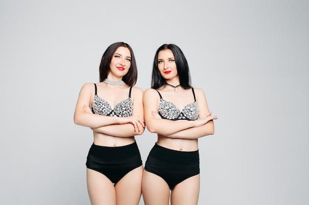 Соблазнительные близнецы в блестящем и гламурном белье позируют со скрещенными руками