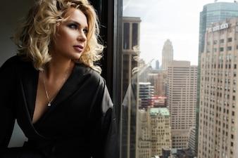Seductive woman in black silk robe sits on a windowsill looking at New York