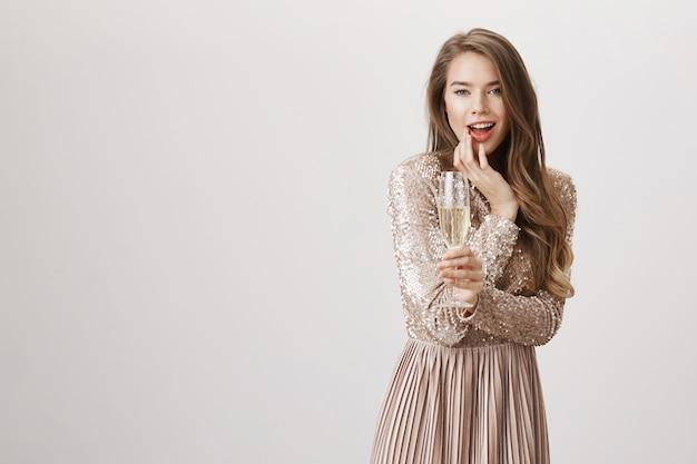 Соблазнительная женщина в вечернем платье пьет шампанское