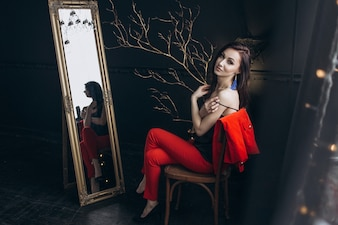 Seductive woman in red suit sits before a mirror