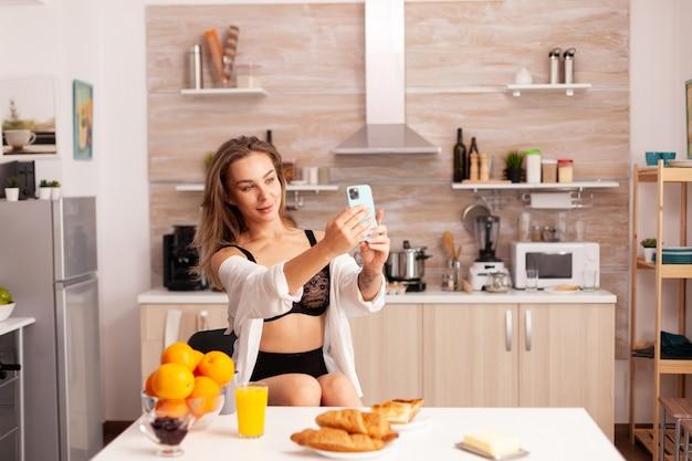 집 부엌에서 스마트폰을 사용하여 셀카를 찍는 섹시한 란제리의 매혹적인 여자. 아침에 템퍼링 속옷을 입고 스마트폰으로 문신을 한 매력적인 여성.
