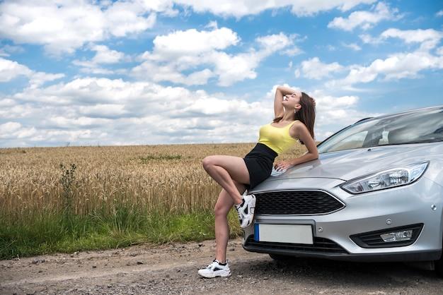 자유를 즐기는 도시 밖에서 여름에 차 근처에서 포즈를 취하는 매혹적인 여자