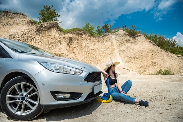 街の外で夏に車の近くでポーズをとる魅惑的な女性