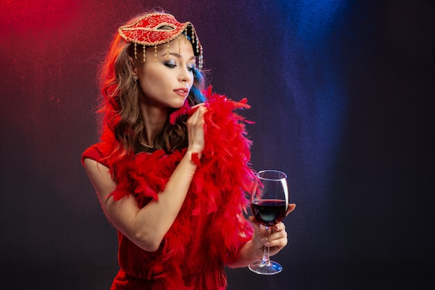 Seductive woman in red fancy dress holding a glass of wine straightens the boa on her shoulders