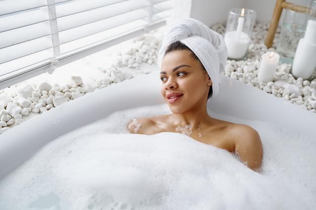 魅惑的な女性は泡風呂でリラックスします。バスタブの女性、スパの美容とヘルスケア、バスルームのウェルネストリートメント、背景の小石とキャンドル