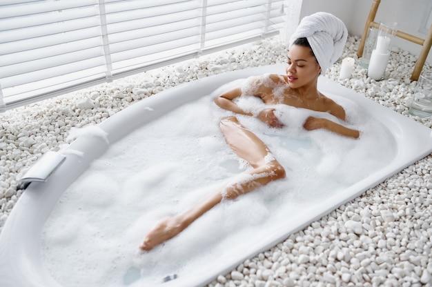 魅惑的な女性は泡でお風呂でリラックスします。バスタブの女性、スパの美容とヘルスケア、バスルームのウェルネストリートメント、背景の小石とキャンドル