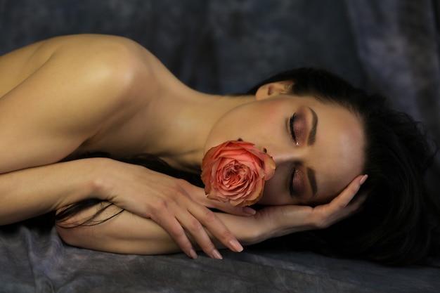 입에 장미와 함께 포즈를 취하는 닫힌된 눈을 가진 매혹적인 여자 프리미엄 사진