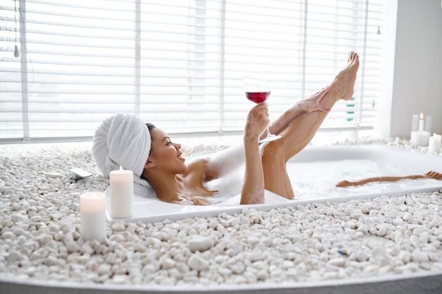 グラスワインを持つ魅惑的な女性は、泡風呂でリラックスします。バスタブの女性、スパの美容とヘルスケア、バスルームのウェルネストリートメント、背景の小石とキャンドル