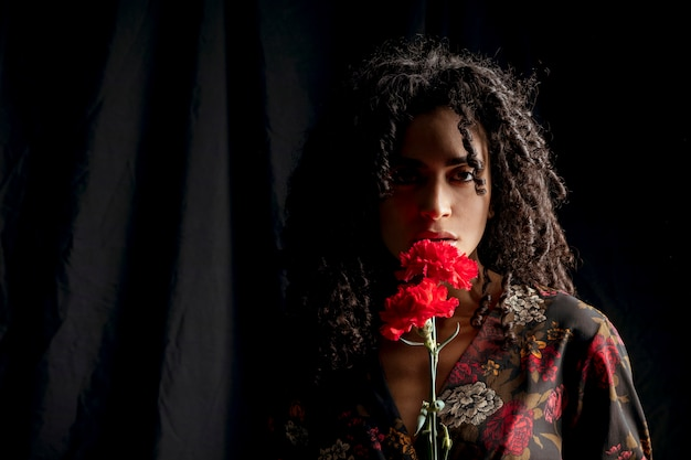 Seductive woman with red flowers in darkness