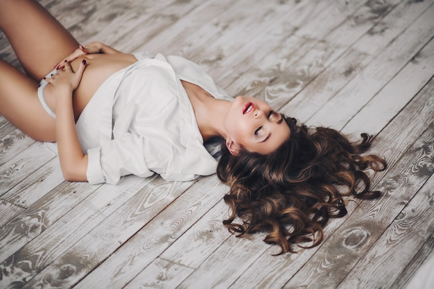 Seductive woman with wavy hair feeling desire on floor with eyes closed Premium Photo