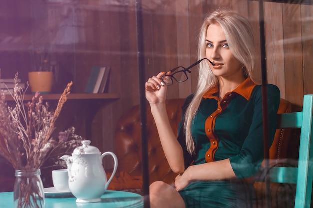 Соблазнительная молодая блондинка в городском кафе. красивая девушка в кафе смотрит прямо.
