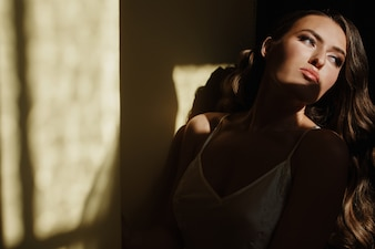 Seductive young bride in a silk dress sits on the windowsill in the early morning