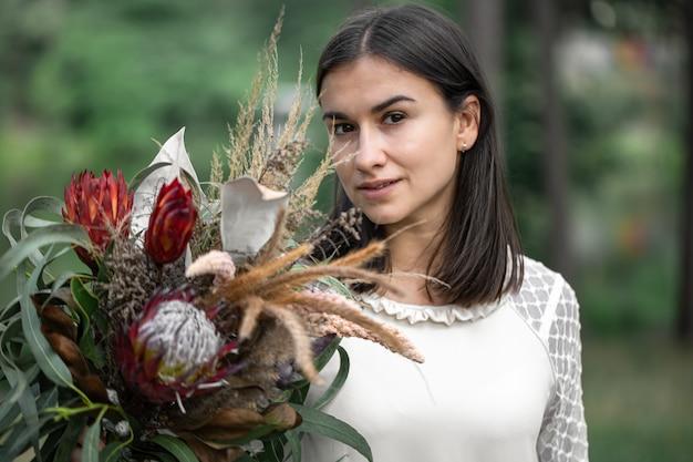 ぼやけた背景に森の花の花束と白いドレスを着た魅惑的な若いブルネットの女性、