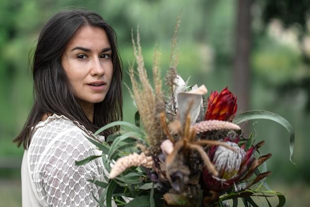 흐릿한 배경에 숲에서 꽃다발을 든 하얀 드레스를 입은 매혹적인 젊은 갈색 머리 여성,