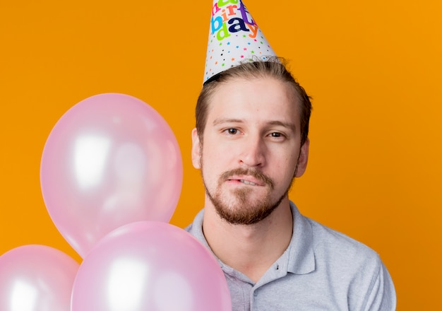 オレンジ色の壁の上に立っている唇の誕生日パーティーのコンセプトを噛む気球の束を保持しているパーティーキャップの魅惑的な若い男