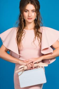 핑크 명품 드레스, 여름 패션 트렌드, 세련된 스타일, 블루 스튜디오 배경, 유행 핸드백을 들고 매혹적인 젊은 세련된 섹시한 여자